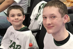 Aidan and Ryker courtside at a Bucks game.