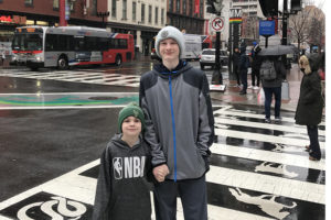 Aidan stands on the streets in Chinatown with his brother, Ryker.