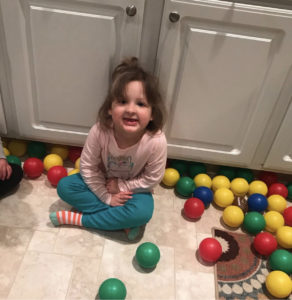 Nora sits on the ground amidst a pile up multi-colored toy balls.