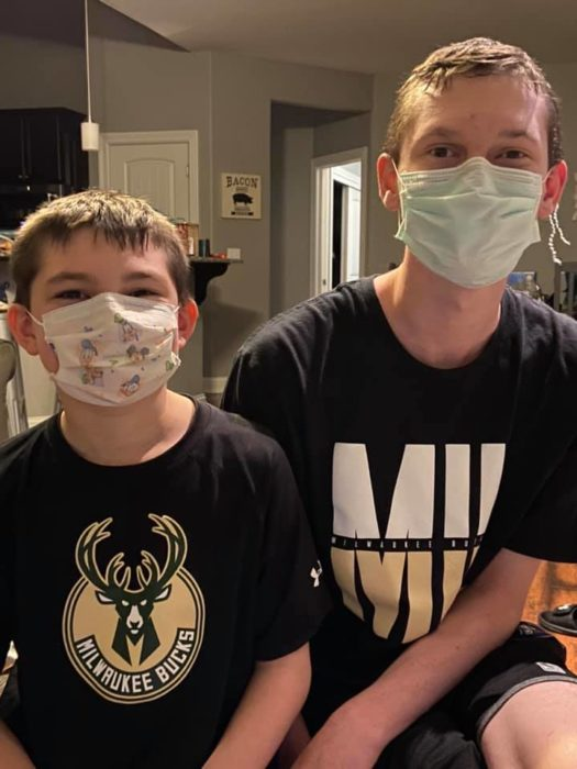 Two boys are wearing face coverings for Covid-19.