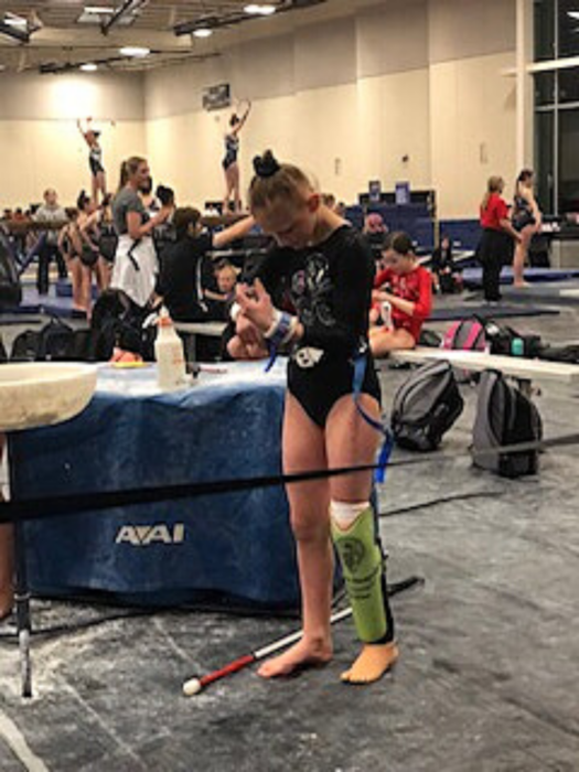 Jordan stands on her prosthetic foot and adjust her wrist bands at a gymnastic competition.